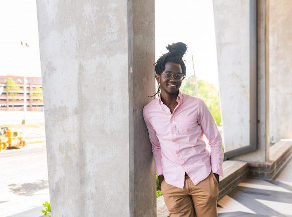Moses Ochola leaning against pillar