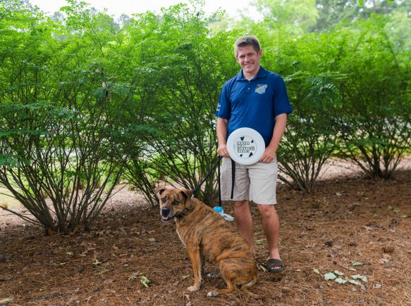 Tristan holding frisbee with dog